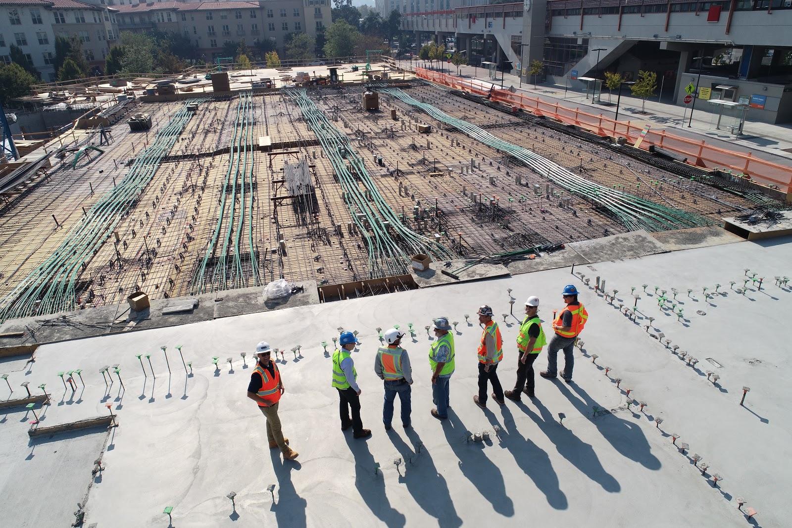 A construction crew stands atop a building and surveys a job site.