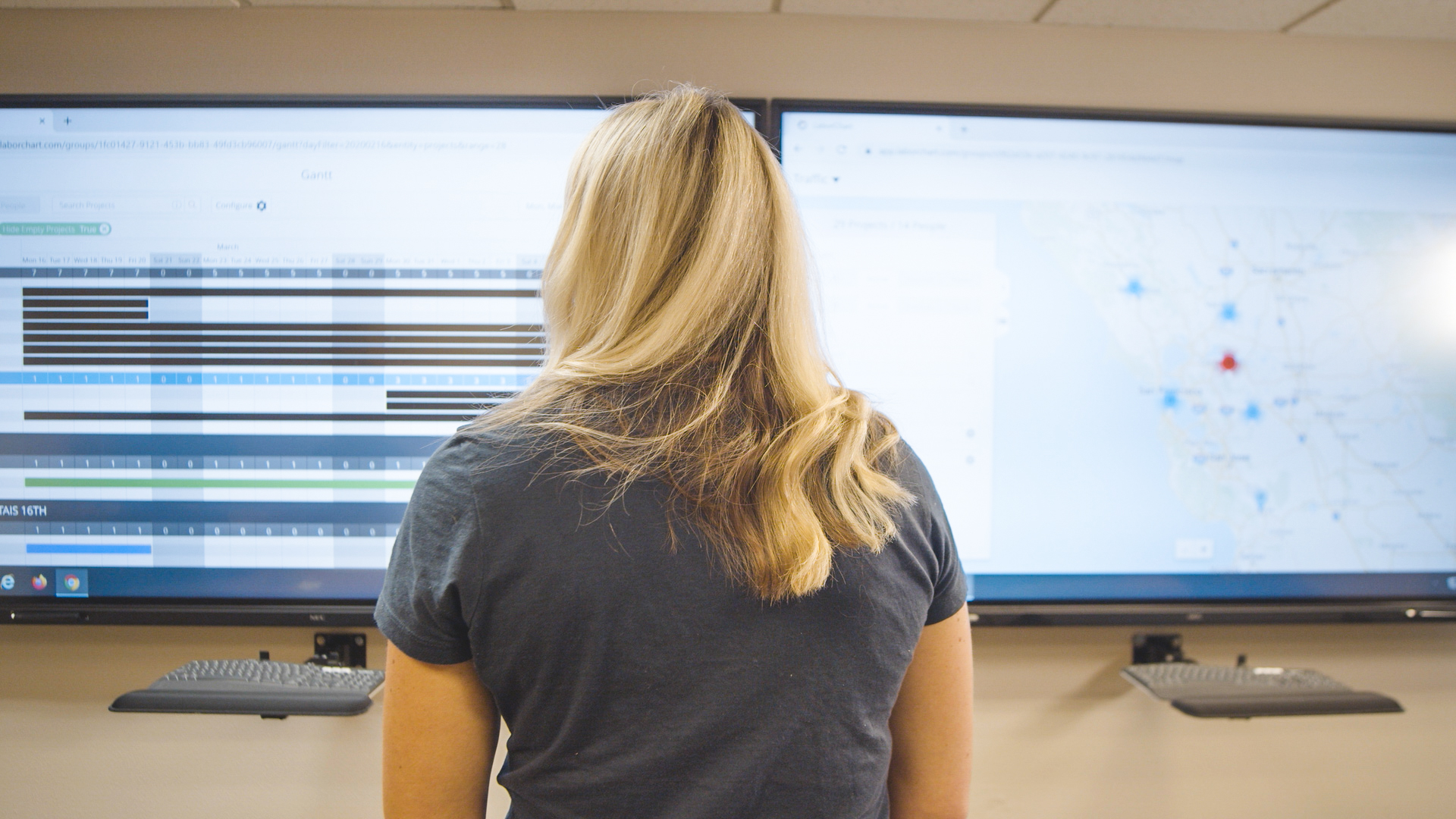 """A labor manager stands in front of two 80"""" screens to manage the workforce of an electrical contractor."""